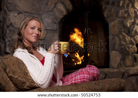 Portrait of a woman sitting in an armchair by a fireplace. She is holding a cup of tea and smiling at the camera. Horizontal format.