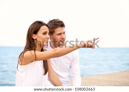 Portrait of a woman sitting on a pier together with her boyfriend pointing toward the sea