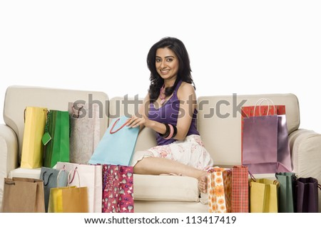 Portrait of a woman sitting on a sofa and holding shopping bag