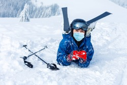 Portrait of a woman skier in medical mask during COVID-19 coronavirus on a snowy mountain at a ski resort