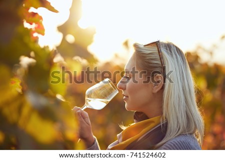 Portrait of a woman tasting white wine in autumn colorful vineyard #741524602