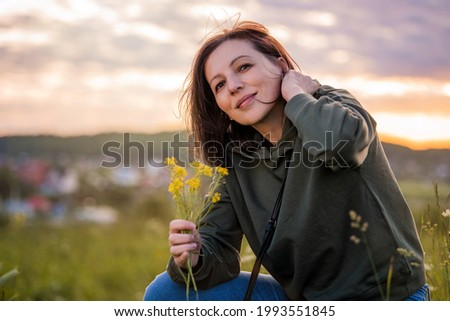 Portrait of a woman traveling on a summer evening against the backdrop of a landscape and sunset.