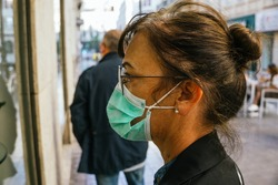 Portrait of a woman window-shopping during the coronavirus pandemic. She is wearing a safety mask. She dresses casually and wears eyeglasses.