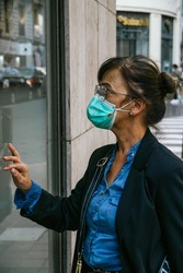 Portrait of a woman window-shopping during the coronavirus pandemic. She is wearing a safety mask. She locks her hand on the window pane. She dresses casually and wears eyeglasses.
