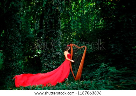 Portrait of a woman with a harp.Beautiful brown-haired woman with a flower wreath on her head,  wearing a red long dress playing the harp in the forest.