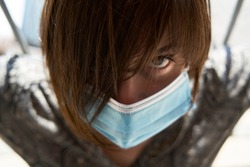 Portrait of a woman with expressive eye and surgical mask for social distancing and prevention during Coronavirus lock down. Frightened by the covid-19, lockdown, social isolation and quarantine