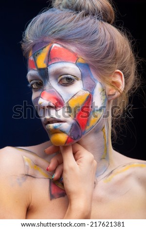 Portrait of a woman with face art.  who is posing covered with blue, red paint