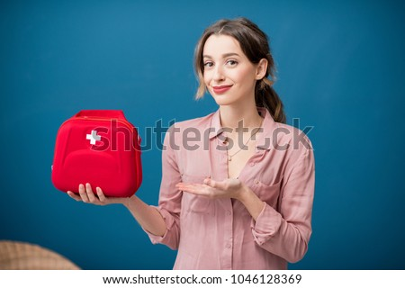 Portrait of a woman with first aid kit on the blue wall background #1046128369