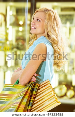 Portrait of a woman with paper bags standing at the shop