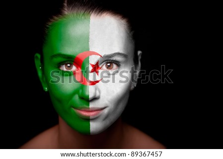 Portrait of a woman with the flag of the Algeria painted on her face.