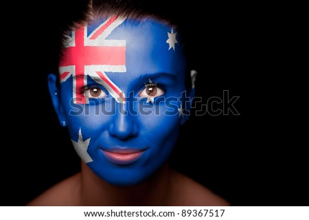 Portrait of a woman with the flag of the Australia painted on her face.