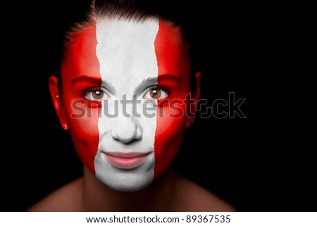 Portrait of a woman with the flag of the Austria painted on her face.