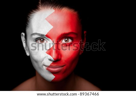Portrait of a woman with the flag of the Bahrain painted on her face.