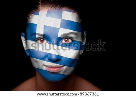 Portrait of a woman with the flag of the Greece painted on her face. - stock photo