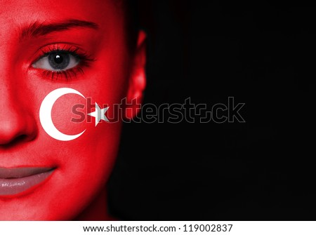 Portrait of a woman with the flag of the turkey painted on her face