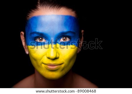 Portrait of a woman with the flag of the Ukraine painted on her face.
