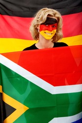 Portrait of a woman with the german flag painted on her face supporting her team in the southafrican world cup 2010