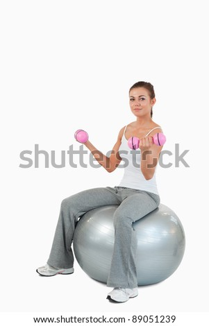 Portrait of a woman working out with dumbbells and a ball against a white background