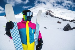 Portrait of a women skier in a multi-colored bright jacket in a ski mask with her face closed on a sunny day against the backdrop of snow-capped Caucasian mountains and clouds