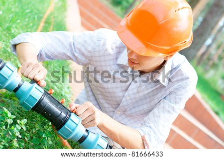 Portrait of a worker repairing a pipe outdoors with copy space
