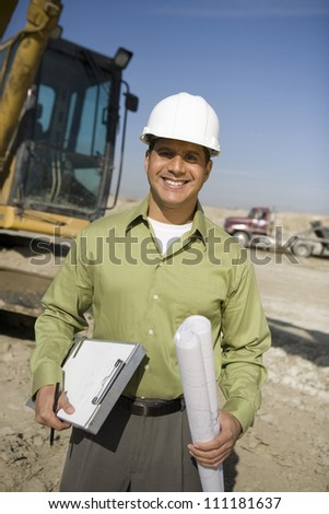 Portrait of a worker wearing hard hat in front of a crane at construction site