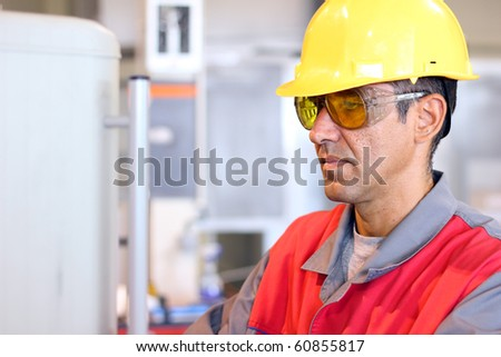 Portrait of a worker wearing protective helmet and safety glasses. CNC machine operator. Industrial worker at work.