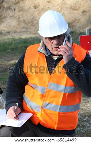 Portrait of a worker with mobile phone on a construction site