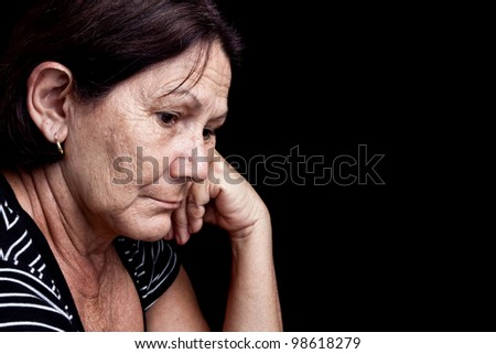 Portrait of a worried old woman with a sad expression isolated on black