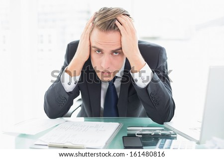 Portrait of a worried young businessman sitting at office desk