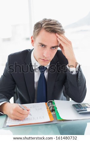 Portrait of a worried young businessman sitting with head in hand at office desk
