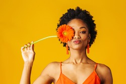 Portrait of a y young woman holding orange Gerbera daisy covering her eye and putting lips sending kiss