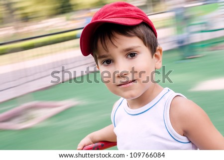 Portrait of a 3-4 years boy playing on the playground with motion blurred background