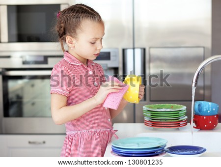 Portrait of a 6 years old girl washing the dishes at home