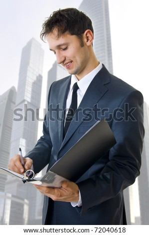 Portrait of a young adult handsome business man filling a form