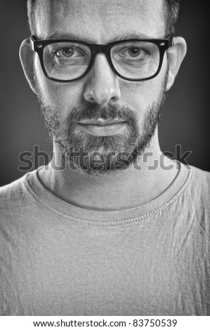 Portrait of a young adult man with beard, wearing glasses