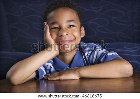 Portrait of a young African American boy sitting in front of a couch with his face propped on his hand. Horizontal shot.