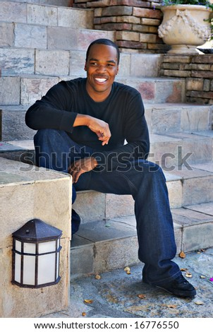 Portrait of a young African American man sitting on rock stairs