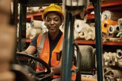 Portrait of a young African female forklift operator moving boxes around a textile warehouse