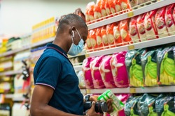 Portrait of a young African man shopping in a department store in supermarket wearing face mask and a modern earbud in ear - concept on business and marketing in covid-19 pandemic
