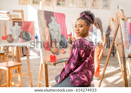 Portrait of a young african student sitting with still life painting at the studio #614274923