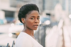 Portrait of a young African woman on a cityscape background, softfocus background