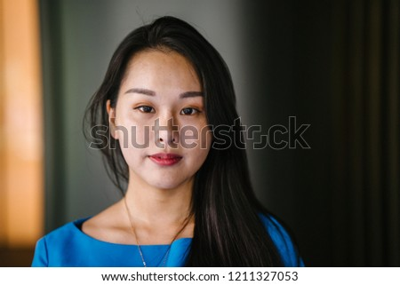 Portrait of a young and attractive Asian Korean woman in a blue top and black dress against a gold metal background. She is smiling softly and exudes confidence, class and elegance. #1211327053