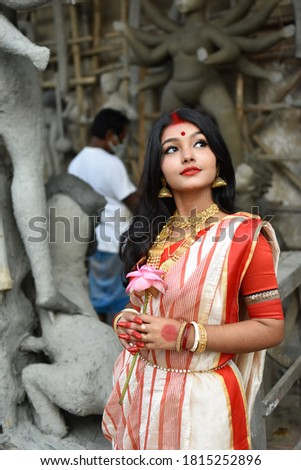Portrait of a young and beautiful Indian woman in red and white traditional ethnic sari and gold jewellery in front of the clay idol of hindu goddess Durga. Indian culture, religion and fashion Zdjęcia stock ©