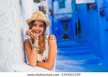 portrait of a young and beautiful woman with hat and white dress, looking to camera with smile and joy, visiting morocco