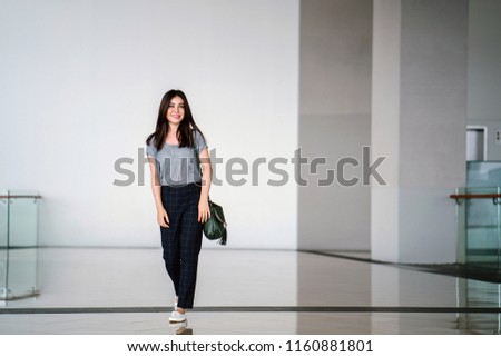 Portrait of a young and cute Japanese Asian woman tourist in a modern, minimalist building. She is casually dressed for travel and is smiling happily.