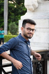 Portrait of a young and handsome Indian Bengali man standing in front of Victoria memorial wearing a blue shirt. Indian lifestyle and fashion