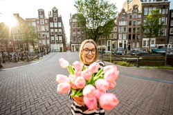 Portrait of a young and happy woman holding a bouquet of pink tulips standing outdoors in Amstredam city