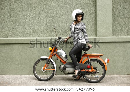 Portrait of a young and stylish woman with a moped.