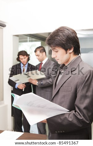 portrait of a young asian businessman with his colleagues in background