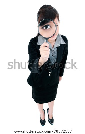 Portrait of a young Asian businesswoman looking through magnifying glass, over white background.